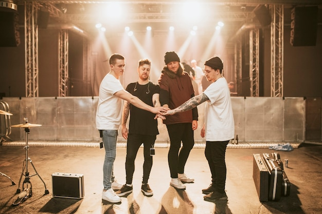 Groupe empilant les mains avant un concert