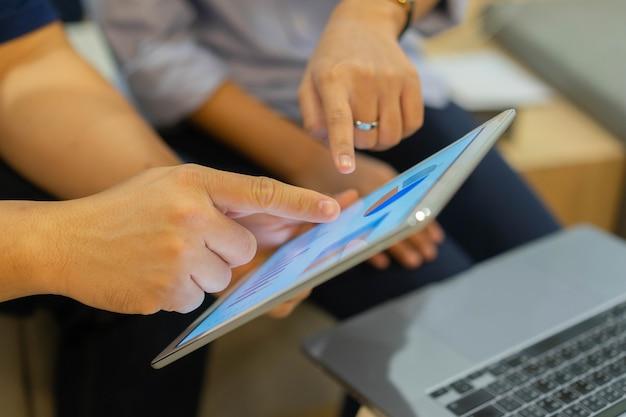 Groupe d'employés point sur l'affichage de la tablette pour consulter les statistiques de stock