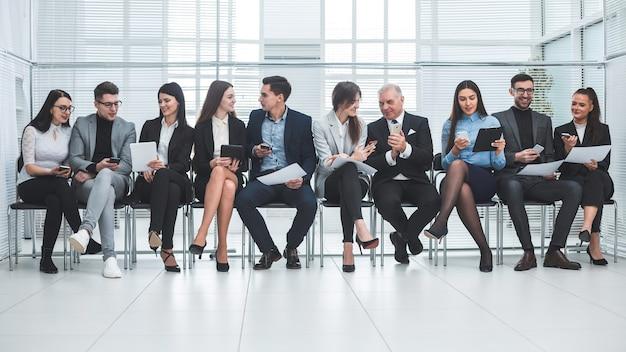 Groupe d'employés utilisant leurs appareils dans la salle de conférence. photo avec une copie de l'espace
