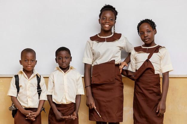 Groupe d'enfants africains debout les uns à côté des autres en classe