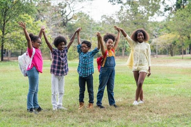 Groupe d'enfants afro-américains levant les mains ensemble dans le parc