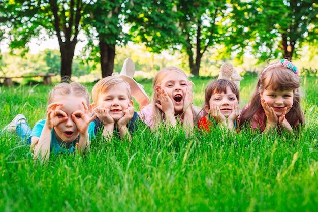 Un groupe d'enfants allongés sur l'herbe verte dans le parc. l'interaction des enfants.