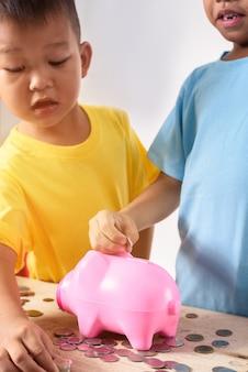 Groupe d'enfants asiatiques aident à mettre des pièces de monnaie dans la tirelire sur fond blanc