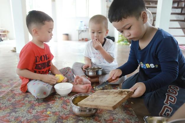 Groupe d'enfants asiatiques préparant de la nourriture et s'amusant à la maison, élève à domicile et concept d'éducation.