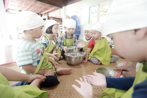 Groupe d'enfants asiatiques préparant de la nourriture et s'amusant à la maison.