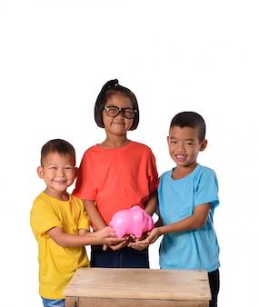 Groupe d'enfants asiatiques s'amuser avec la tirelire isolé sur fond blanc