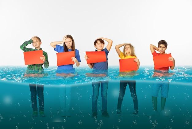 Groupe d'enfants avec des bannières rouges vierges debout dans l'eau de la fonte des glaciers, réchauffement climatique