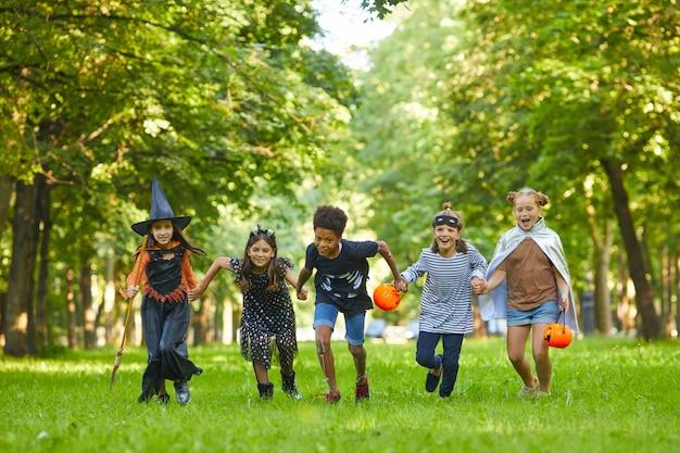 Groupe d'enfants en costumes d'halloween en cours d'exécution sur l'herbe verte dans le parc, ils s'amusent à la fête