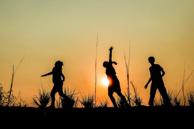 Groupe d'enfants en cours d'exécution sur prairie, coucher de soleil, silhouette en cours d'exécution