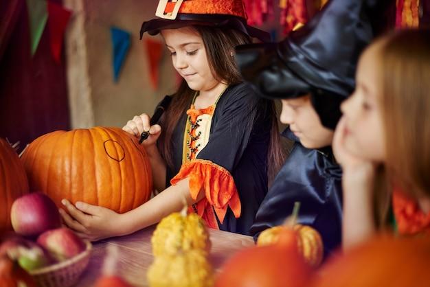 Groupe d'enfants décorant des citrouilles d'halloween