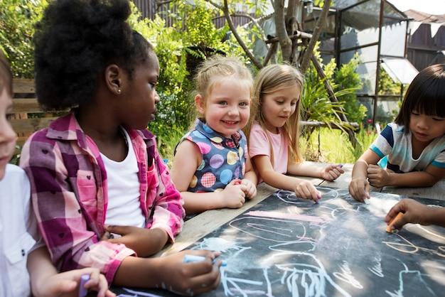 Groupe d'enfants divers dessinant au tableau ensemble