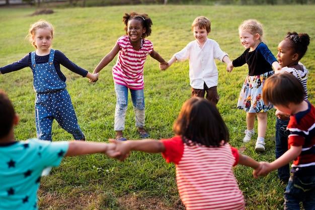Groupe d'enfants divers jouant ensemble sur le terrain