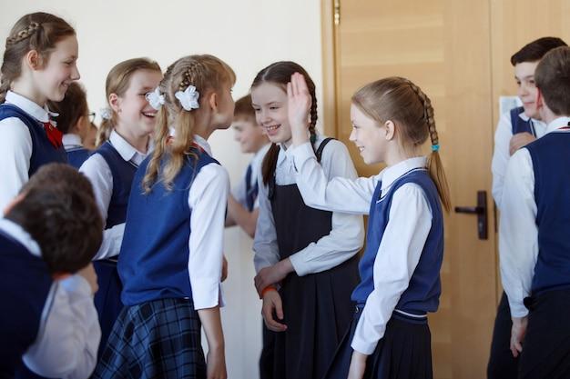 Groupe d'enfants de l'école élémentaire debout dans le couloir de l'école