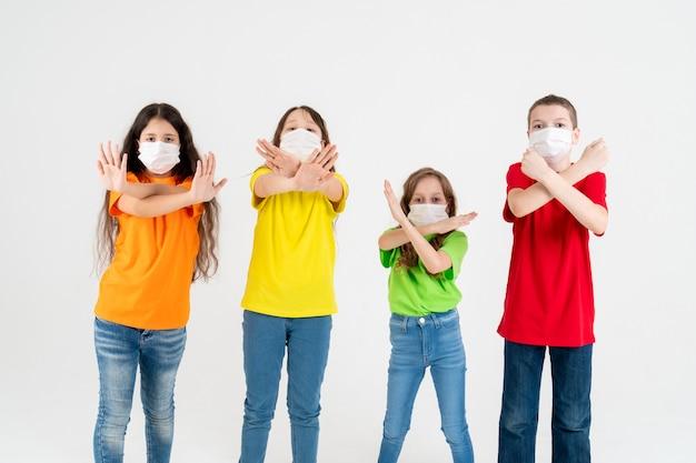 Groupe d'enfants d'écoliers en t-shirts colorés et masques médicaux montrant les mains croisées