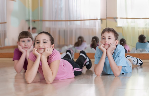 Groupe d'enfants engagés dans un entraînement physique dans le gymnase. horizontal.