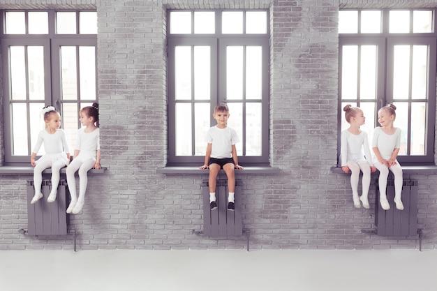 Groupe d'enfants garçons et filles dansant dans une salle de classe blanche ou un studio souriant et s'embrassant ensemble