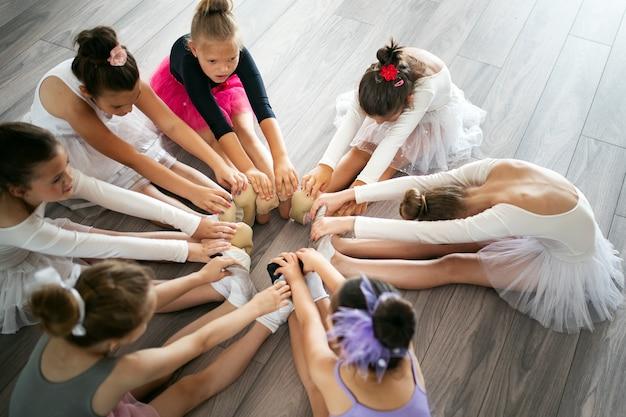 Groupe d'enfants heureux en forme exerçant le ballet en studio ensemble