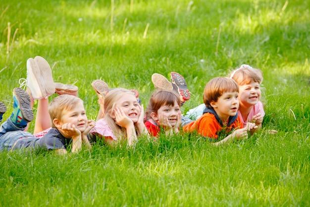 Un groupe d'enfants heureux, garçons et filles, allongés dans le parc sur l'herbe par une journée d'été ensoleillée.