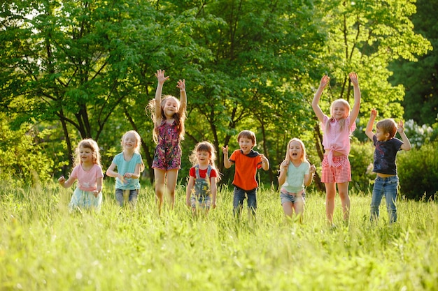 Un groupe d'enfants heureux, garçons et filles, courant dans le parc sur l'herbe par une journée d'été ensoleillée.