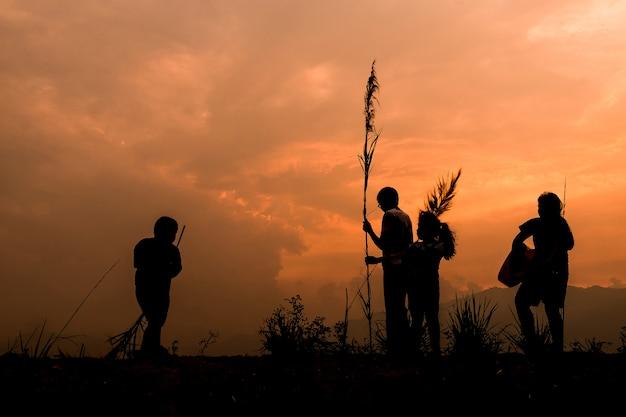 Groupe d'enfants heureux jouant sur la prairie au coucher du soleil, silhouette