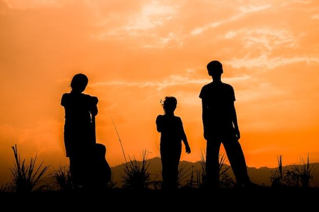 Groupe d'enfants heureux jouant sur prairie au coucher du soleil