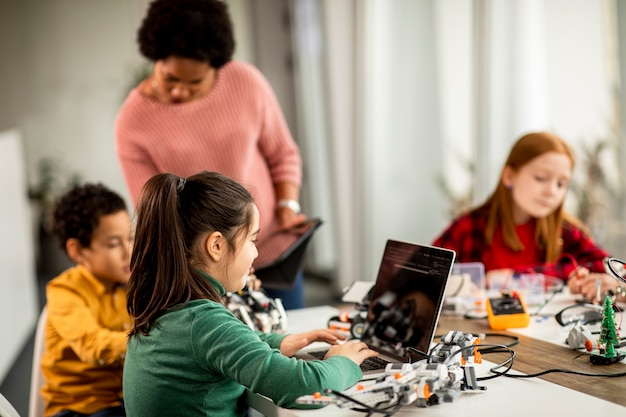 Groupe d'enfants heureux avec leur professeur de sciences afro-américaine avec des jouets électriques de programmation d'ordinateur portable et des robots en classe de robotique