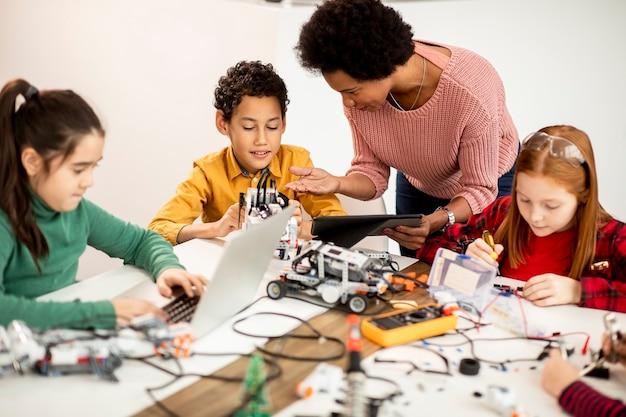 Groupe d'enfants heureux avec leur professeur de sciences afro-américaine