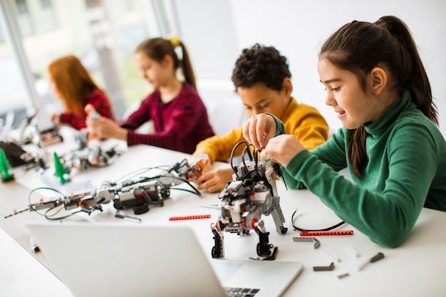 Groupe d'enfants heureux de programmer des jouets électriques et des robots en classe de robotique