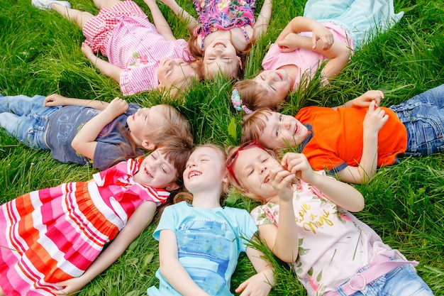 Un groupe d'enfants jouant et courant dans le parc sur un gozon vert.