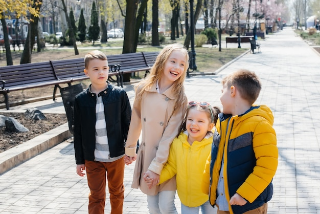 Un groupe d'enfants joue ensemble et marche dans le parc en se tenant la main. amis, enfants.