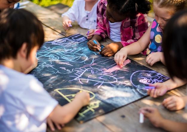 Groupe d'enfants de maternelle amis dessin classe d'art en plein air