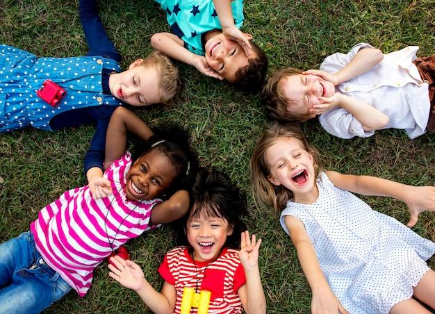 Groupe d'enfants de la maternelle couchés sur l'herbe au parc et se détendre en souriant