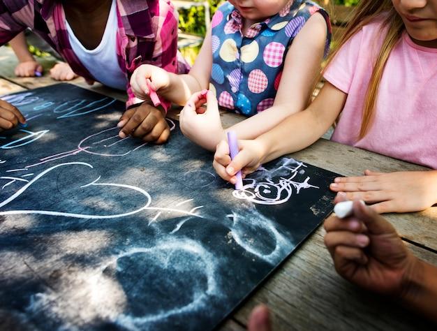 Groupe d'enfants de maternelle enfants dessinant des cours d'art en plein air