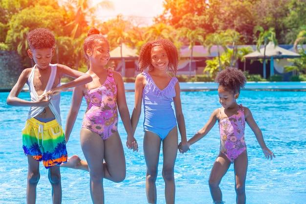 Groupe d'enfants noirs heureux de jouer au parc aquatique en plein air pendant la saison estivale chaude