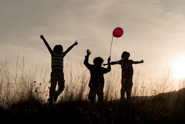 Groupe d'enfants profitant de leur temps sur la prairie au coucher du soleil