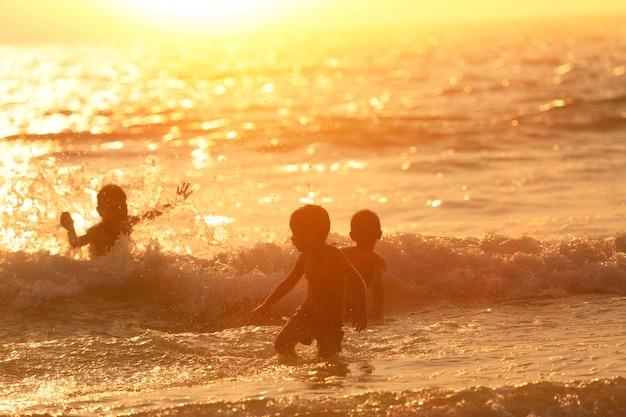 Groupe d'enfants qui jouent sur la plage au coucher du soleil.