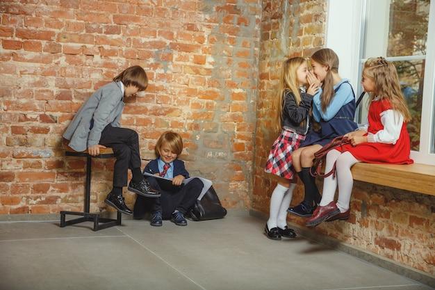Groupe d'enfants qui passent du temps ensemble après l'école. beaux amis au repos après les cours avant de commencer à faire leurs devoirs. intérieur loft moderne. temps scolaire, amitié, éducation, concept de convivialité.