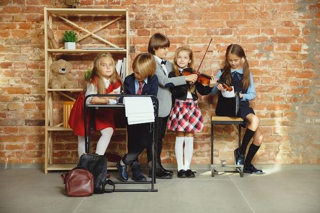 Groupe d'enfants qui passent du temps ensemble après l'école. beaux amis au repos après les cours avant de commencer à faire leurs devoirs