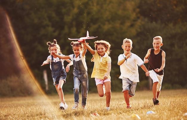 Groupe d'enfants s'amusant à l'extérieur avec un avion jouet rouge dans les mains.