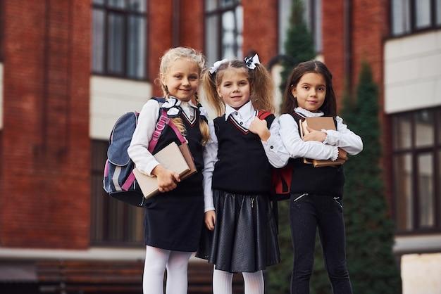 Groupe d'enfants de sexe féminin en uniforme scolaire qui est à l'extérieur ensemble près du bâtiment de l'éducation.