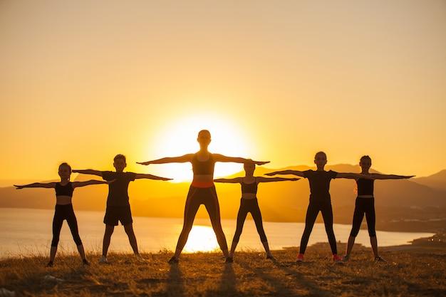 Groupe d'enfants sont engagés dans le yoga avec un entraîneur sur l'océan.