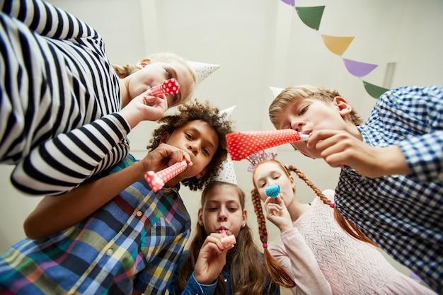 Groupe d'enfants soufflant des cornes de fête
