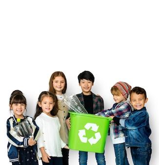 Groupe d'enfants tenant la corbeille avec le symbole de recyclage sur fond noir