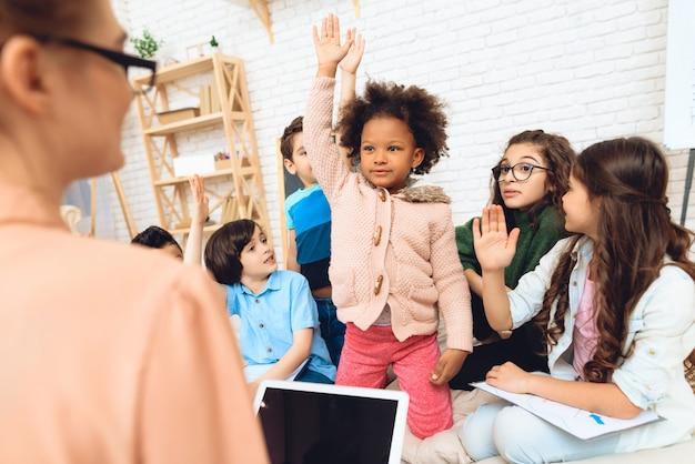 Un groupe d'enfants tire les mains pour répondre à l'enseignant.