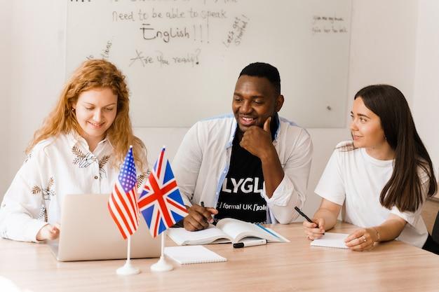 Un groupe d'enseignants attrayant multiethnique en ligne étudie et rit, discute de quelque chose