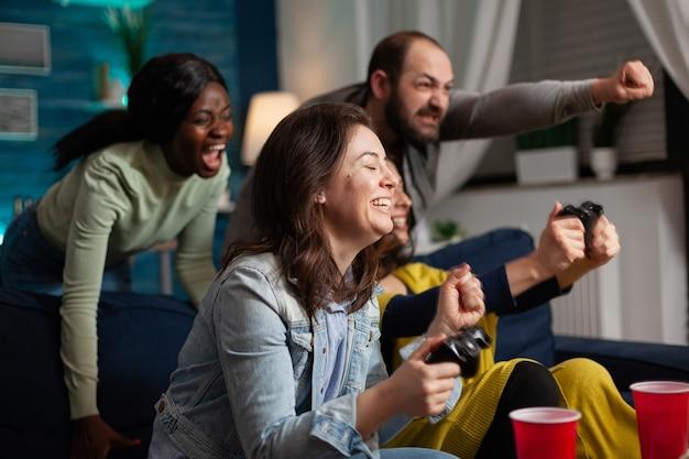 Groupe enthousiaste d'amis multiethniques célébrant la victoire après avoir gagné aux jeux vidéo en ligne à l'aide d'une manette sans fil, tard dans la soirée en train de socialiser assis sur un canapé.