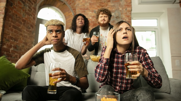 Groupe enthousiaste de personnes regardant le championnat de match de sport à la maison