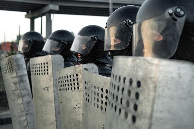 Groupe d'escouades de police en tenue anti-émeute debout en rang et tenant des boucliers tout en se protégeant contre les émeutes