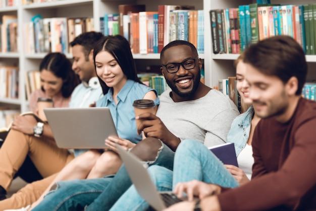 Groupe d'ethnie multiculturelle souriant et parlant en bibliothèque