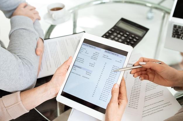 Groupe d'êtres humains discutant d'un document financier électronique sur l'écran de la tablette numérique à la réunion de travail